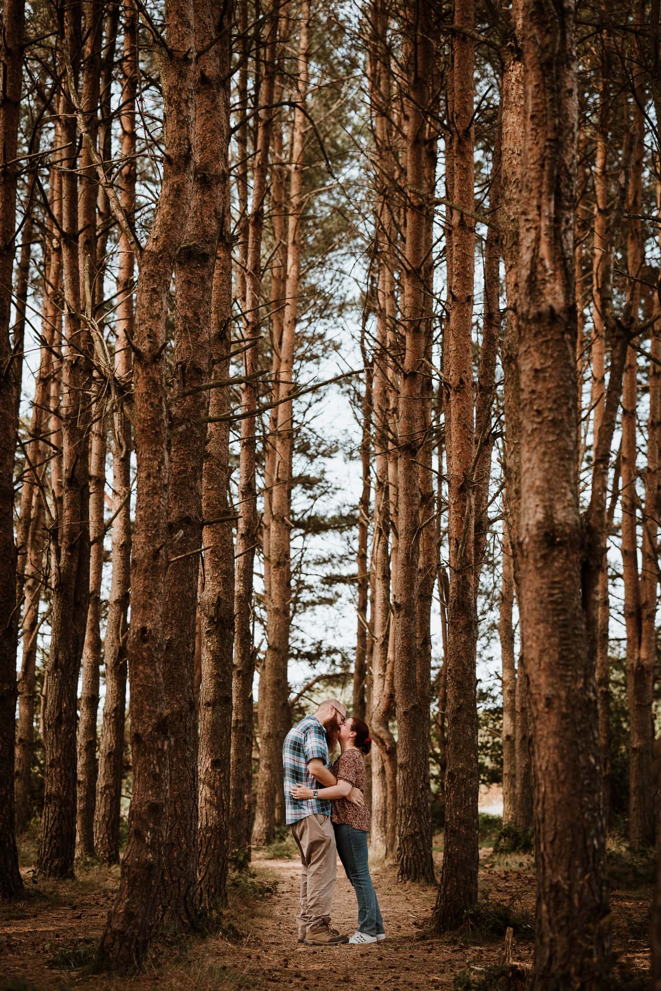 Couple kiss between tall woodland trees during engagement shoot