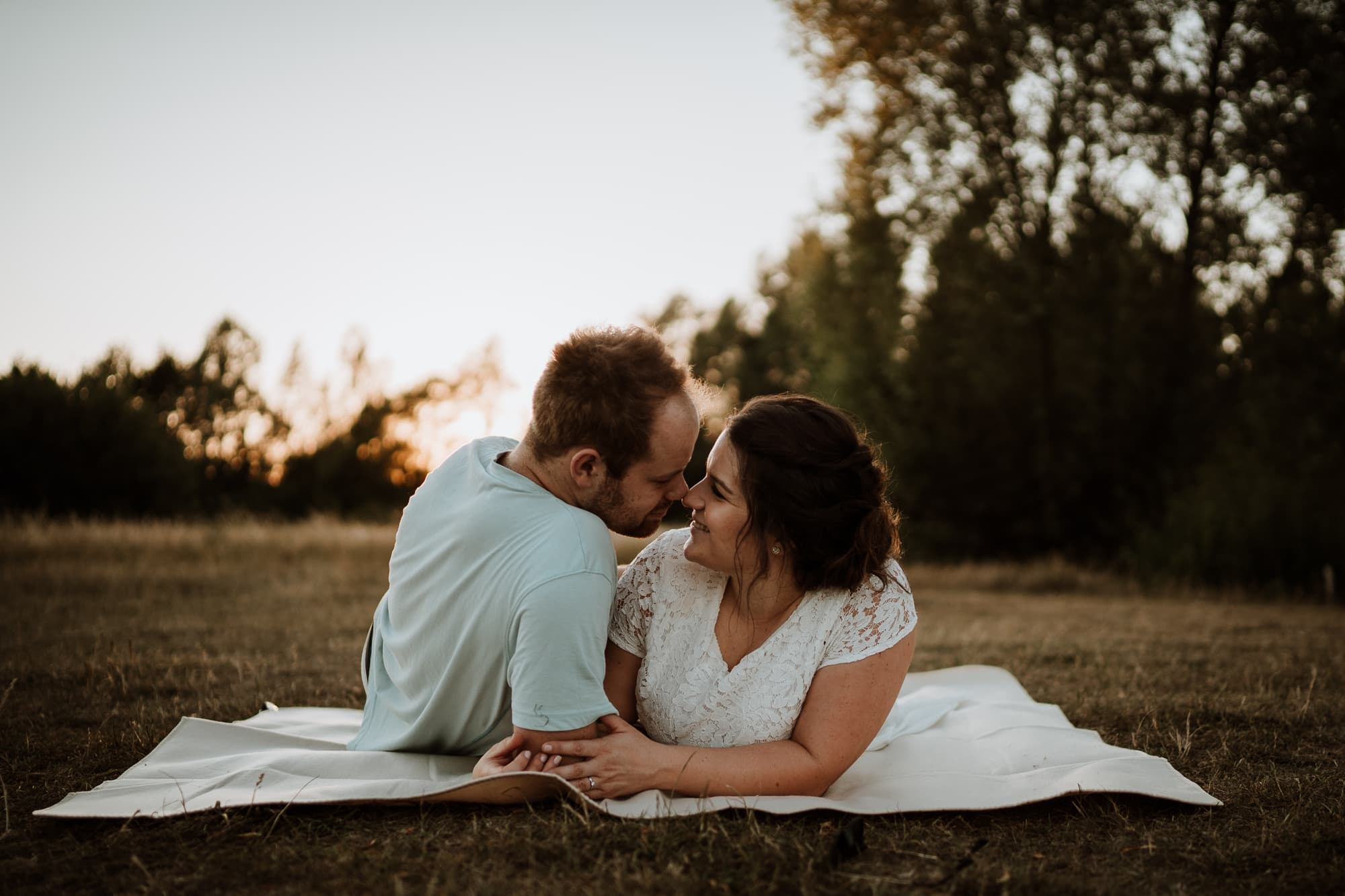 Couple kissing laying on blanket at sunset