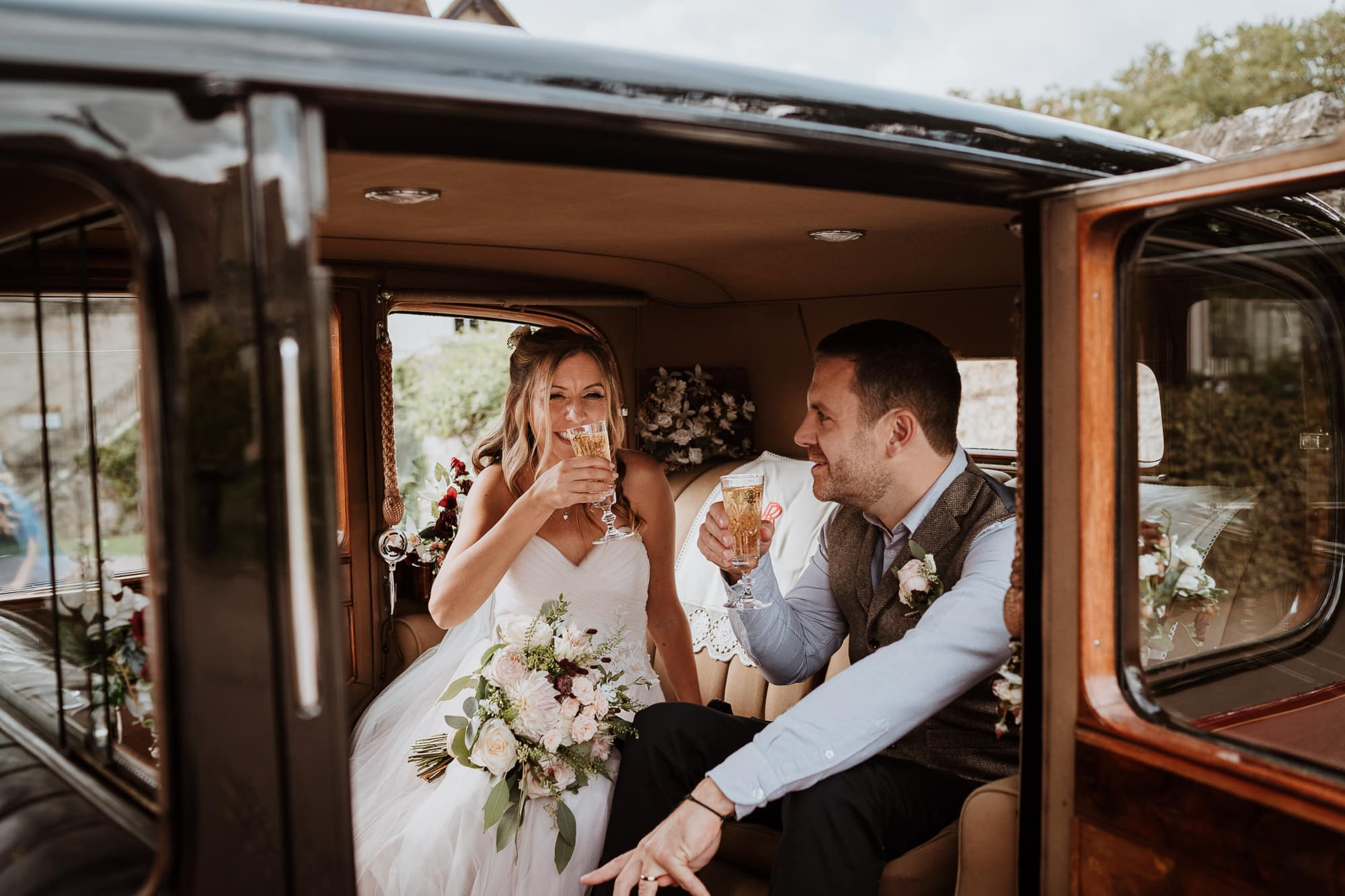 Bride and Groom raising a glass of Champagne in the back of their Wedding car