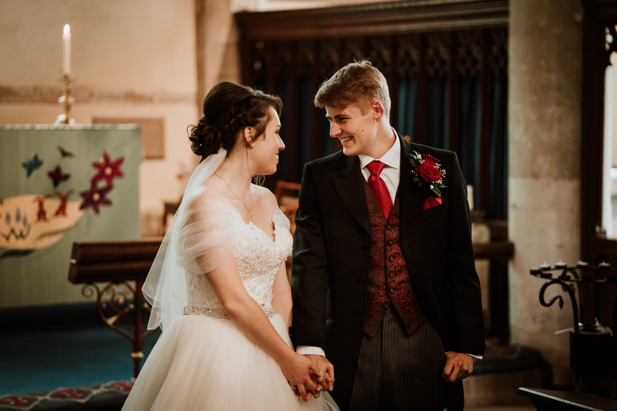 Bride and Groom holding hands and smiling at each other in the Church