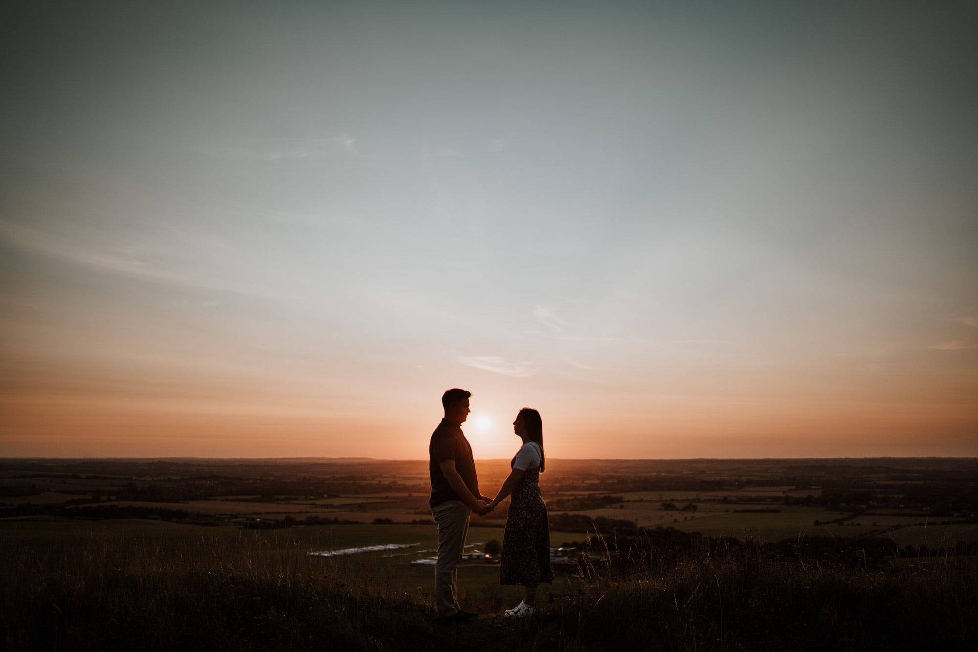 Engaged couple standing on Dunstable Downs at Sunset
