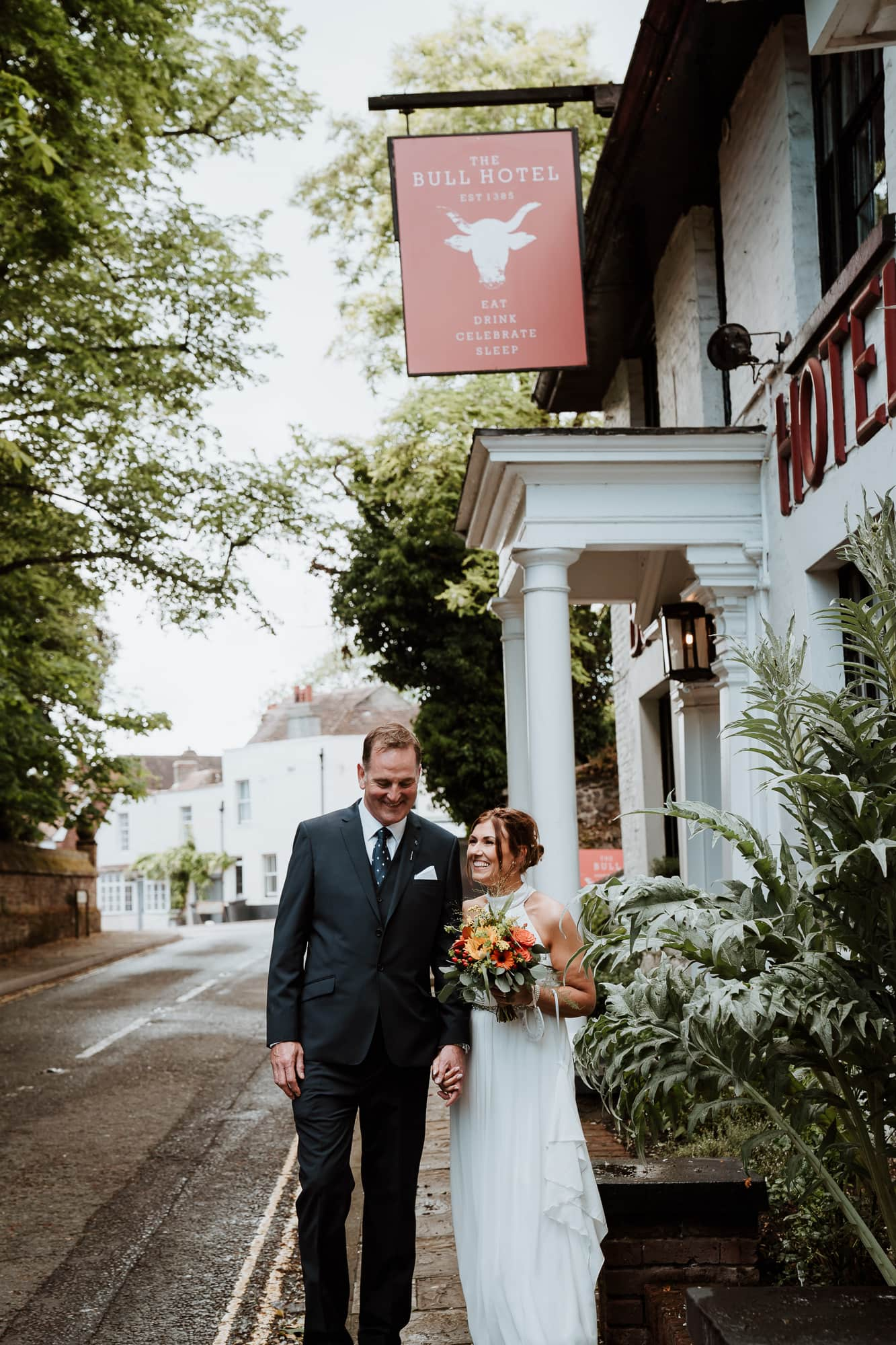 Bride and Groom laughing together at the doors of The Bull Hotel