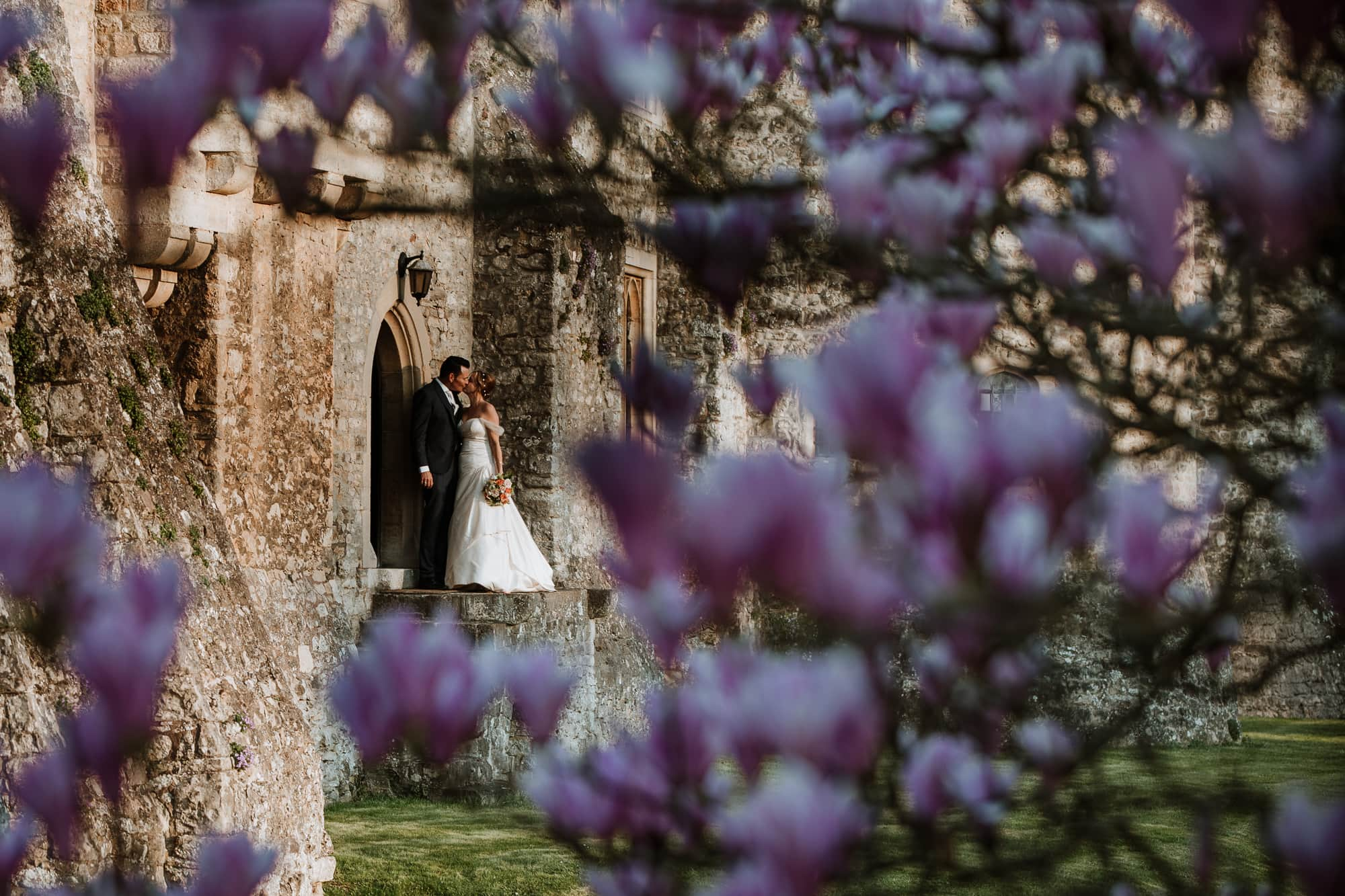 Bride and Groom kissing during their portraits in the grounds of Allington Castle