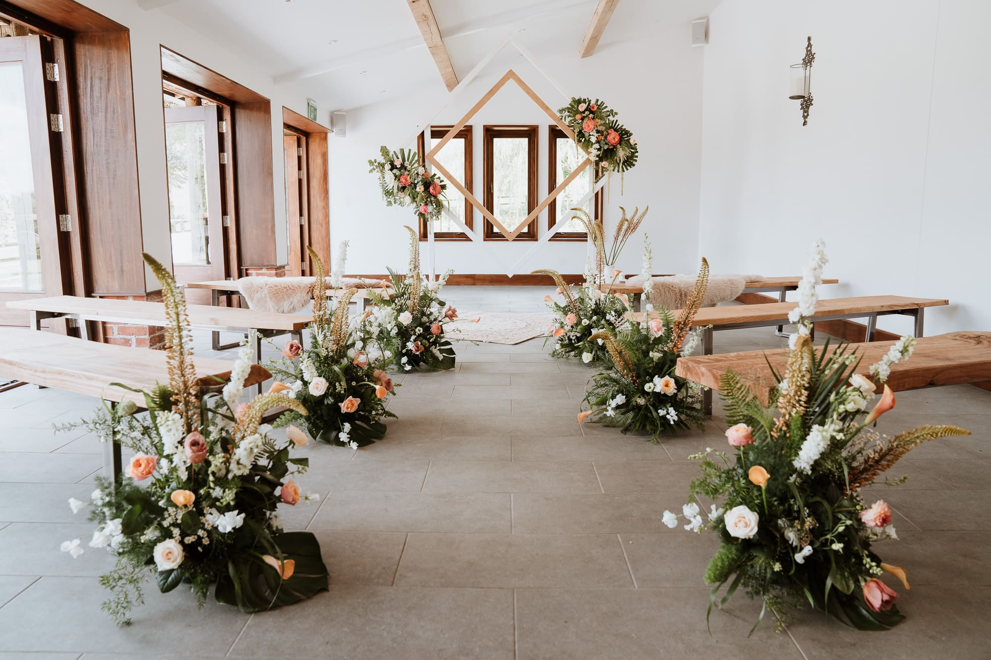 The ceremony area at The Oak Barn dressed for a wedding with stunning florals