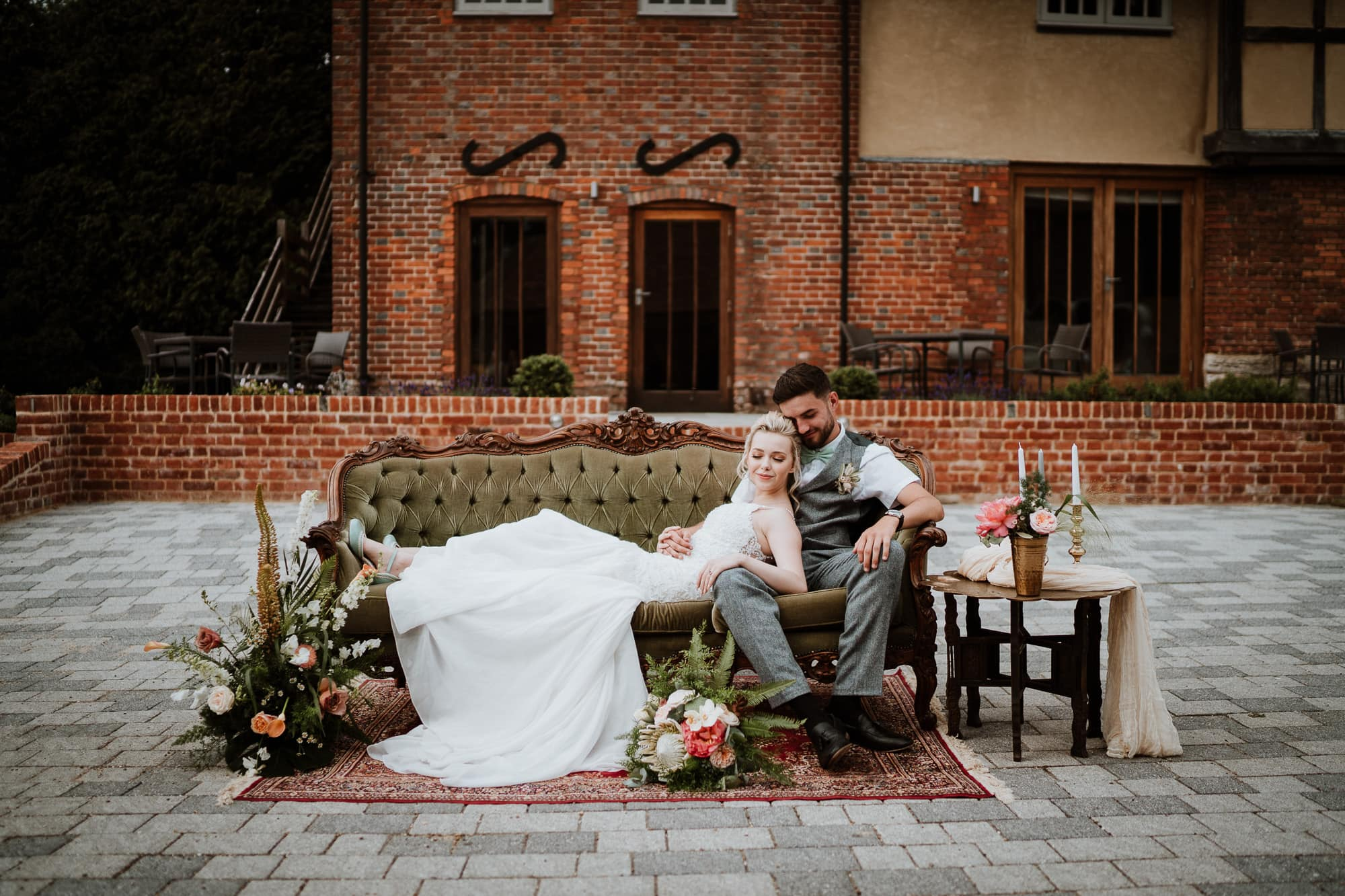 Bride laying on Groom on sofa with stunning floral details at The Oak Barn