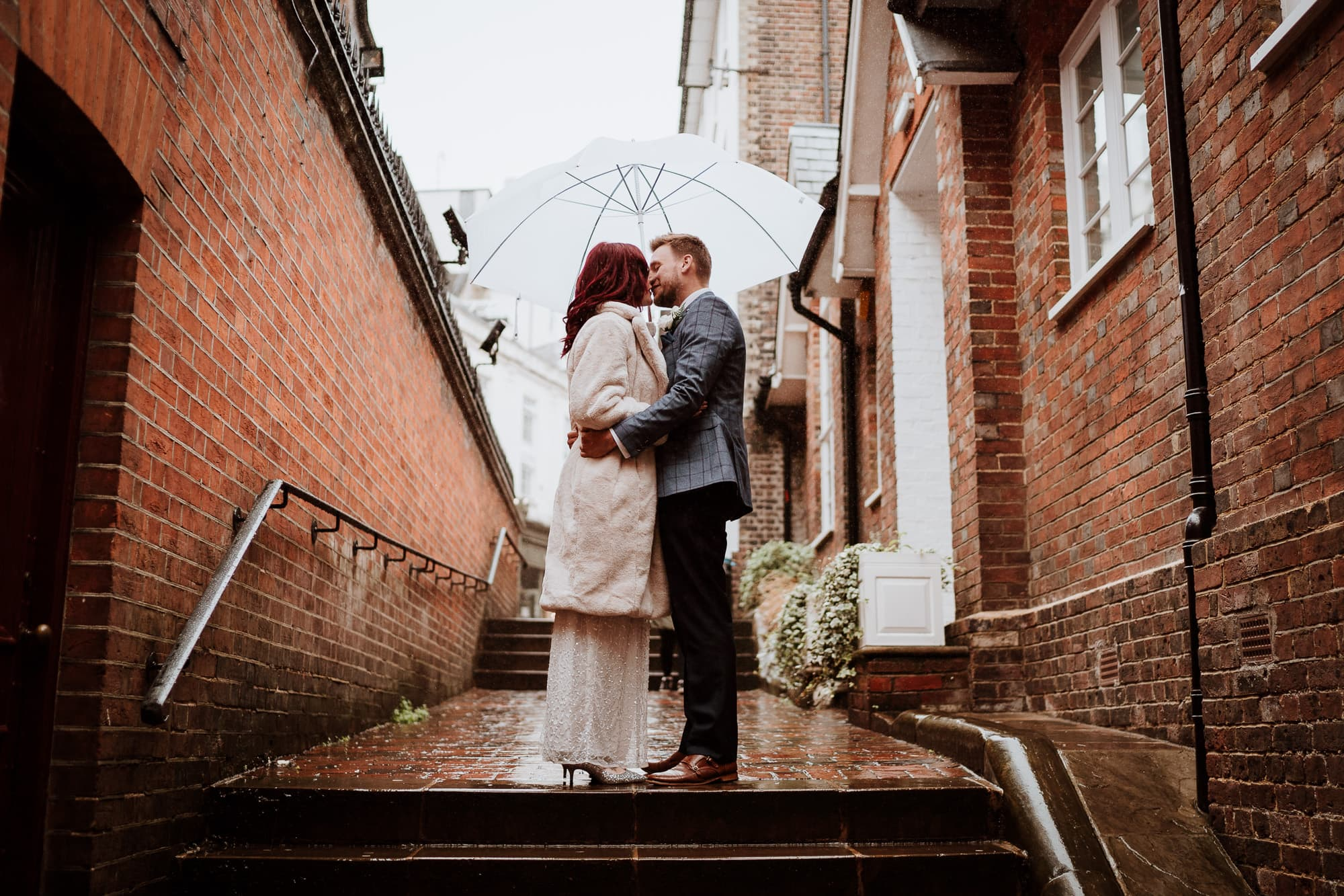 Bride and Groom kissing under umbrella in The Pantiles