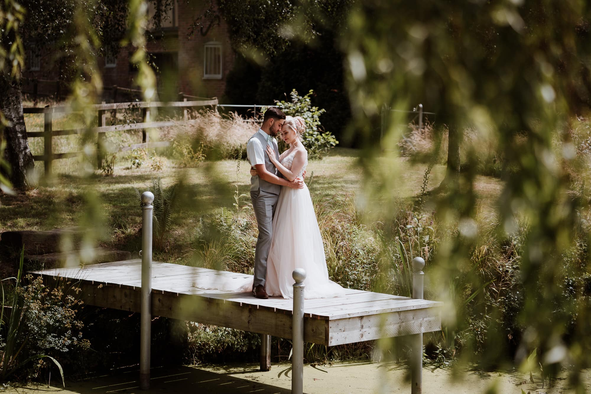 Bride and Groom hugging during portraits on a wooden jetty