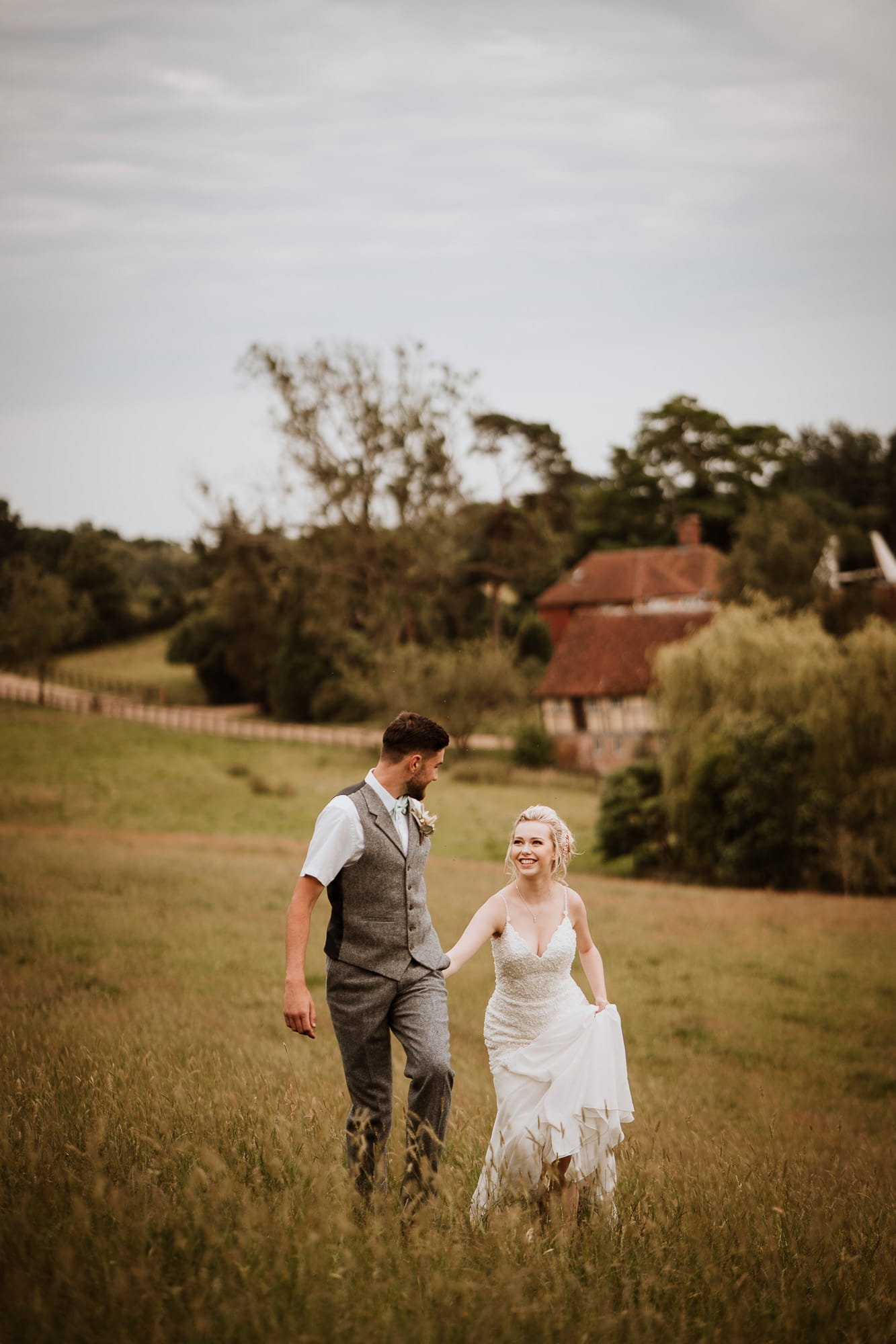 Groom leads Bride up a grassy hill with the Oak Barn Wedding venue in the background