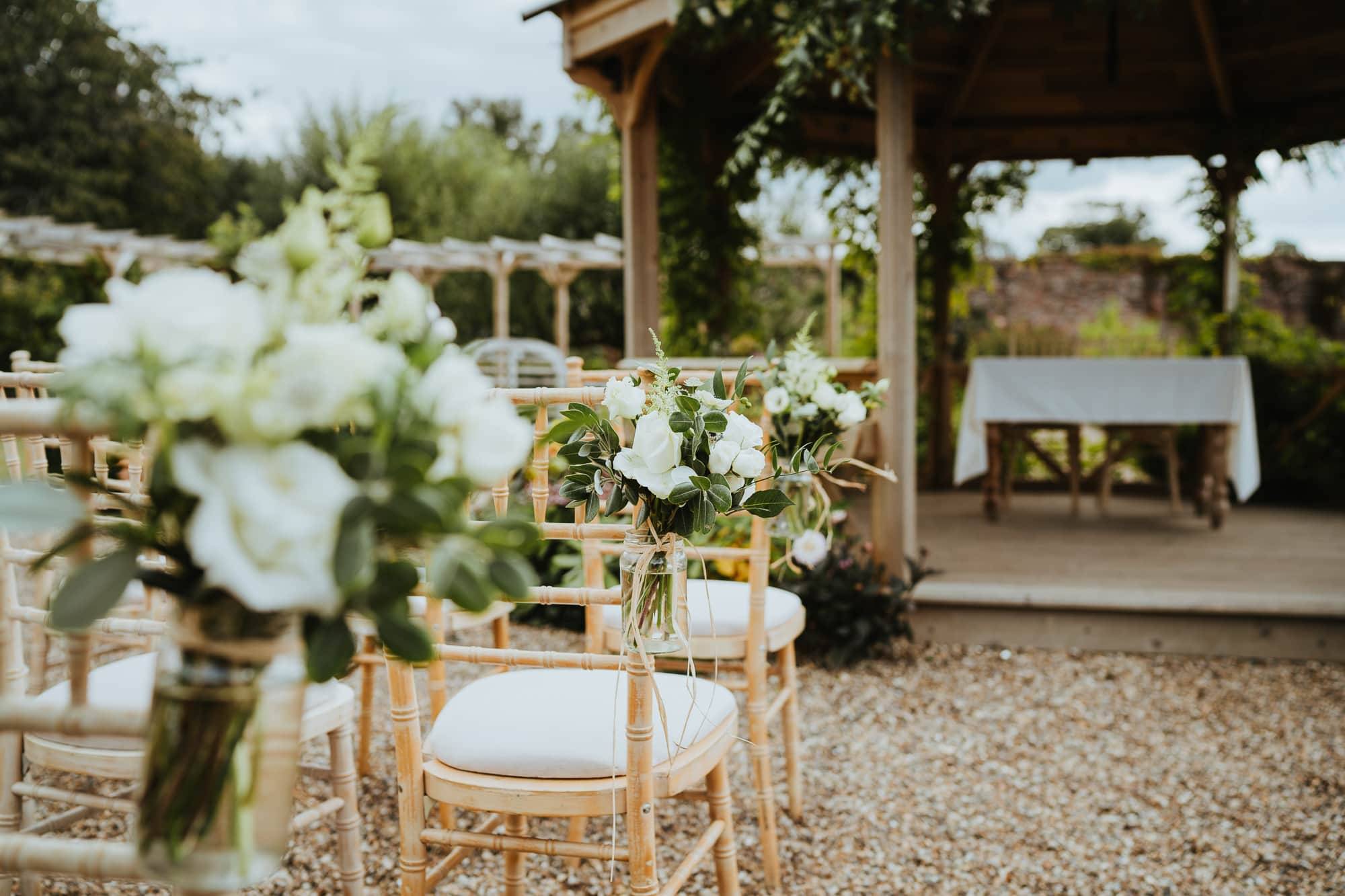 Rustic chairs dressed for an intimate wedding ceremony at The Secret Garden