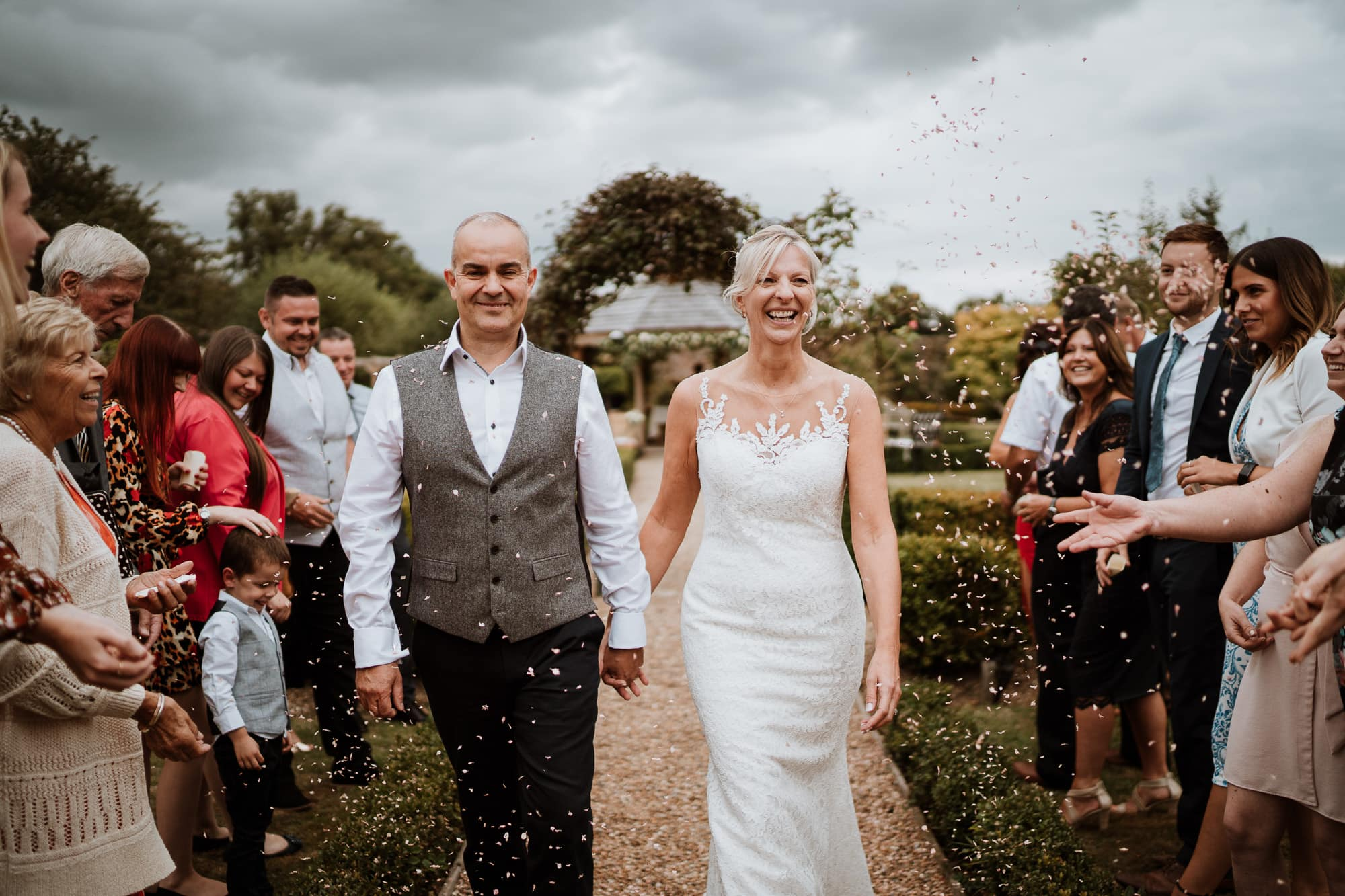 Bride and Groom smiling as they walk through a tunnel of confetti at The Secret Garden