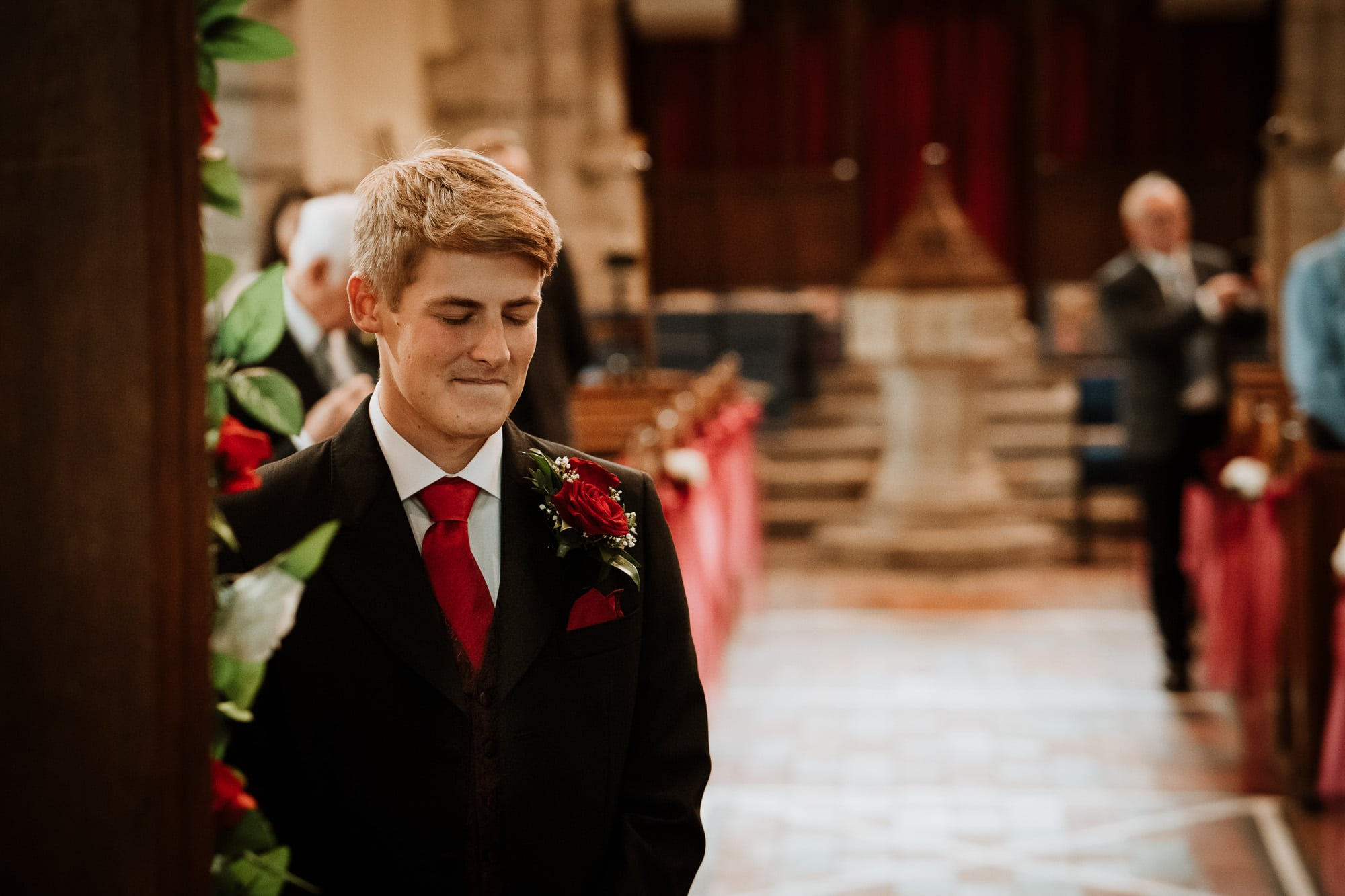 Groom nervously waiting for his bride to walk down the aisle at Shorne Church