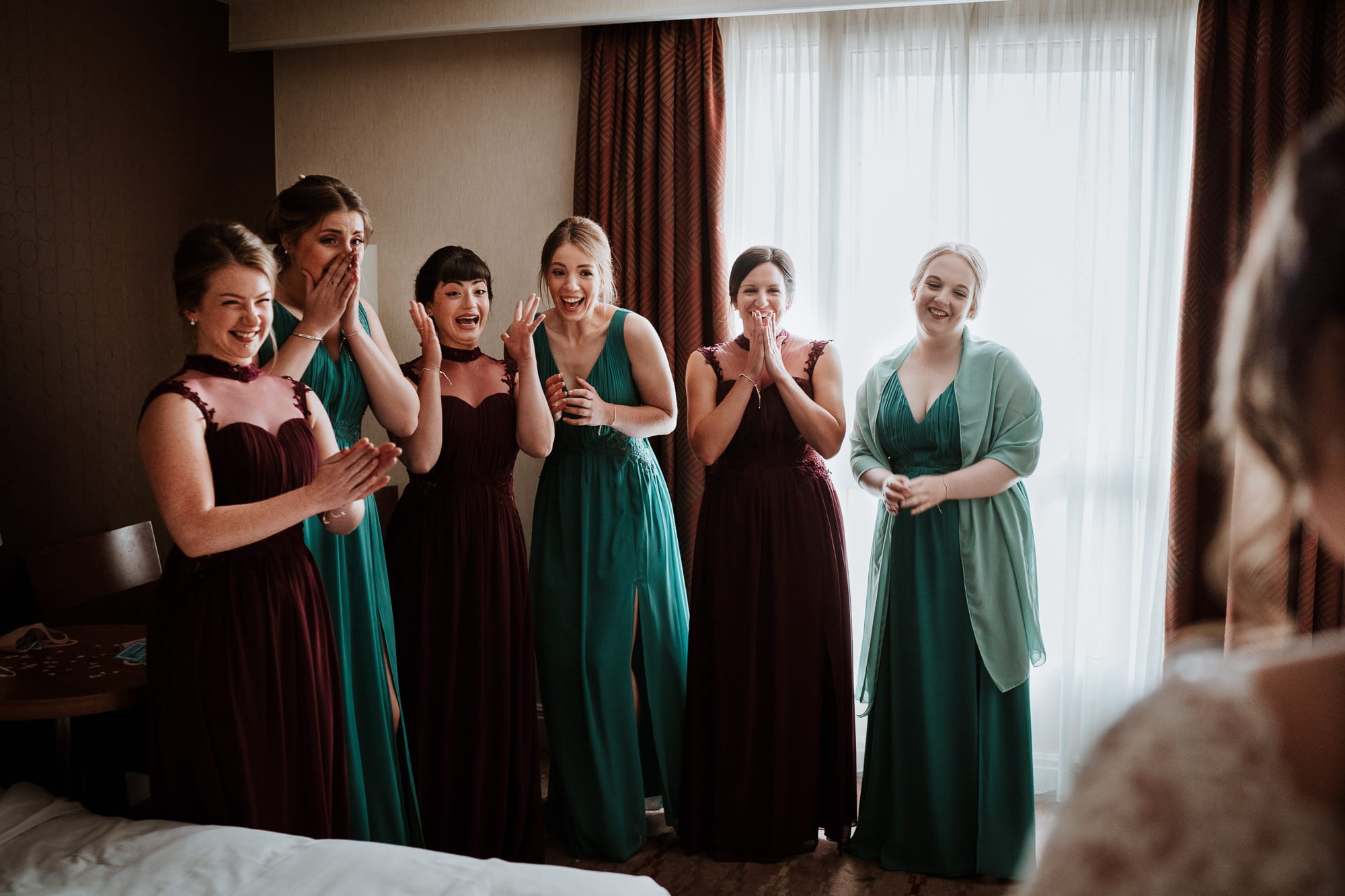 Documentary style photography of bridesmaids seeing bride for the first time