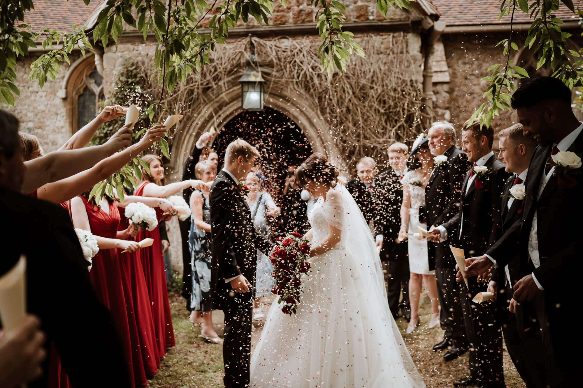 Kent Wedding and Bride and groom showered with confetti outside Shorne Church